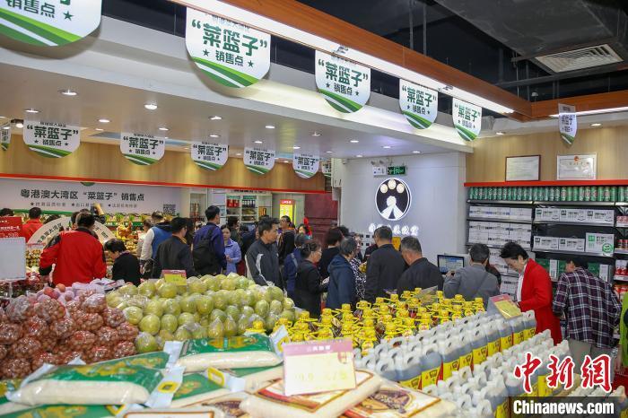 """广州华景新城一家""""肉联帮""""社区生鲜店被周边居民挤得水泄不通。 程景伟 摄"""